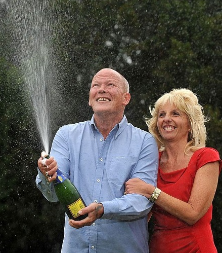 Dave and Angela Dawes popping champagne
