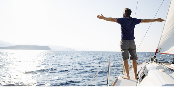 Freedom, the traveller millionaire, man standing on yacht with outstretched arms