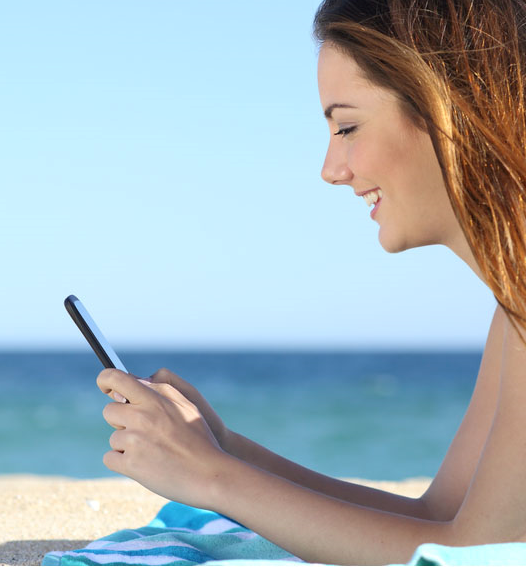 Play the lotto on your mobile, pretty woman using smartphone on beach
